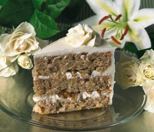 image on page for  Hummingbird Cake (Seasonal: February-April)  / perceived to contain Cake, Dessert, Food, Torte, Blossom, Flora, Flower, Plant, Cream, Creme, Flower Arrangement, Ornament, Icing, Petal, Flower Bouquet, Dahlia, Leaf, Lily